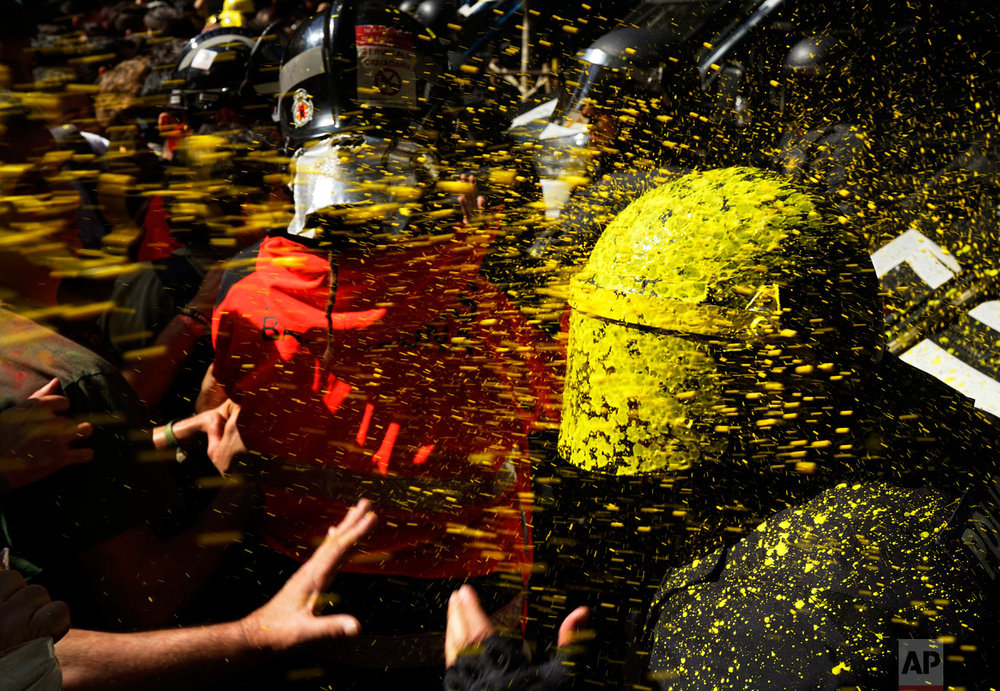 Pro-independence demonstrators throw paint at Catalan police officers during clashes in Barcelona, Spain, on Saturday, Sept. 29, 2018. Catalan separatists clashed with police on Saturday in downtown Barcelona as tensions increase before the anniversary of the Spanish region's referendum on secession that was outlawed and ended in violent raids by security forces. (AP Photo/Daniel Cole)