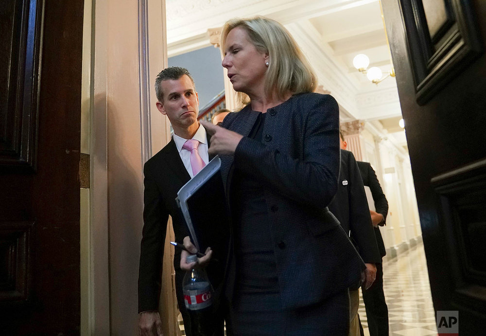 Homeland Security Secretary Kirstjen Nielsen, foreground, talks with Max Schachter, left, father of Alex Schachter, who was killed during the Marjory Stoneman Douglas High School shooting, at a meeting of the Federal Commission on School Safety, Aug. 16, 2018, in Washington. (AP Photo/Pablo Martinez Monsivais)