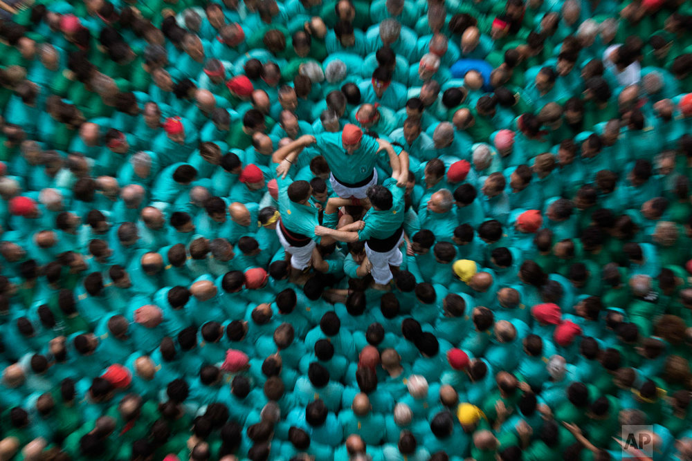 "Members of the ""Castellers de Villafranca"" try to complete their human tower during the 27th Human Tower Competition in Tarragona, Spain, Oct. 7, 2018. (AP Photo/Emilio Morenatti)"