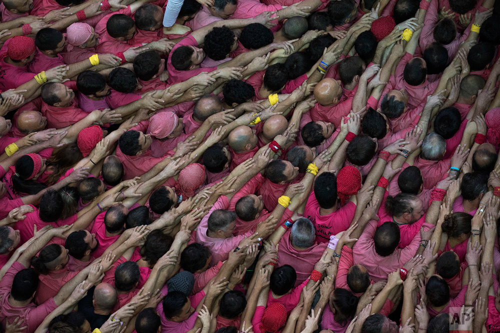 "Members of the ""Colla Vella dels Xiquests de Valls"" try to complete their human tower during the 27th Human Tower Competition in Tarragona, Spain, Oct. 7, 2018. (AP Photo/Emilio Morenatti)"