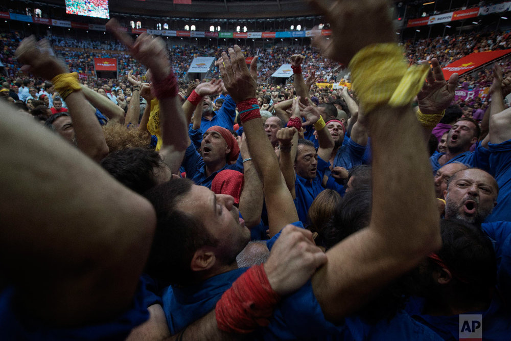"Members of the ""Castellers d'Esplugues "" celebrate after completing their human tower, during the 27th Human Tower Competition in Tarragona, Spain on Oct. 6, 2018. (AP Photo/Emilio Morenatti)"