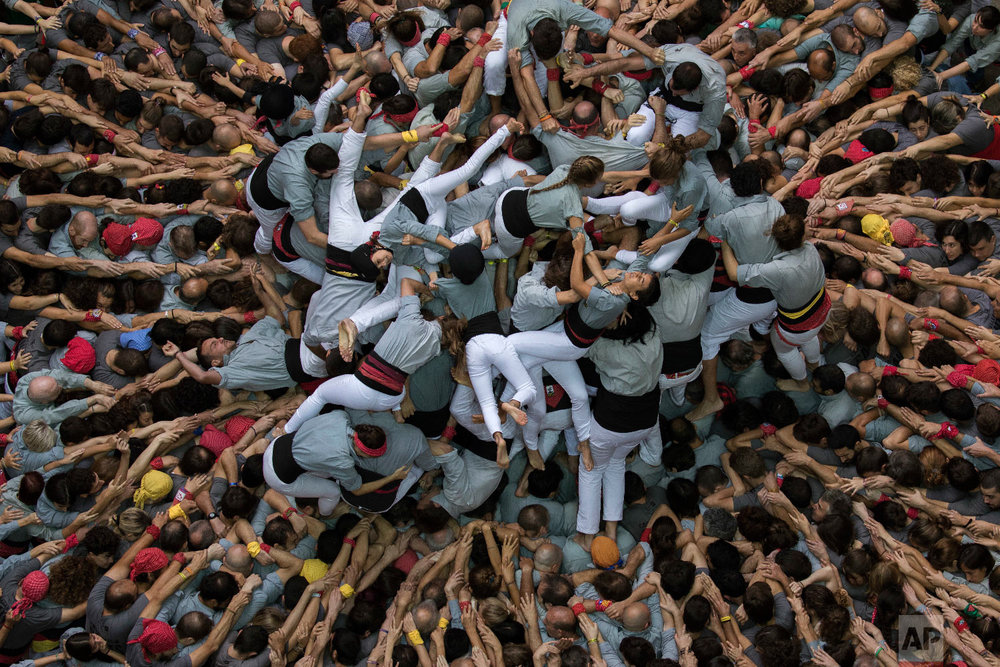 "Members of ""Castellers de Sants"" fall as they try to complete their human tower during the 27th Human Tower Competition in Tarragona, Spain, Oct. 7, 2018. (AP Photo/Emilio Morenatti)"