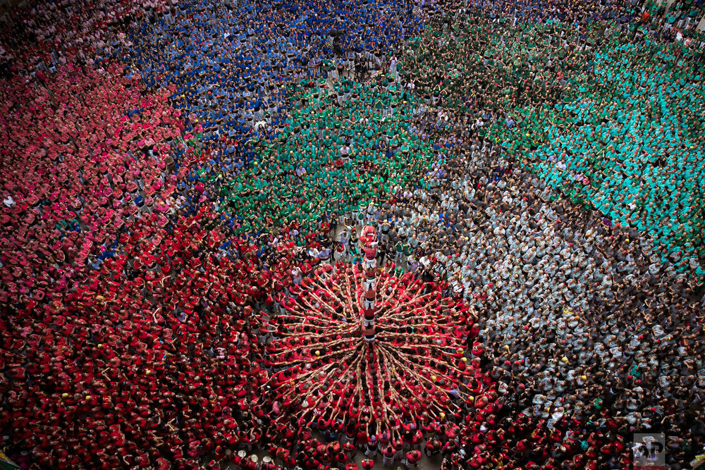 "Members of the ""Colla Joves Xiquets de Valls"" complete their human tower during the 27th Human Tower Competition in Tarragona, Spain, Oct. 7, 2018. (AP Photo/Emilio Morenatti)"