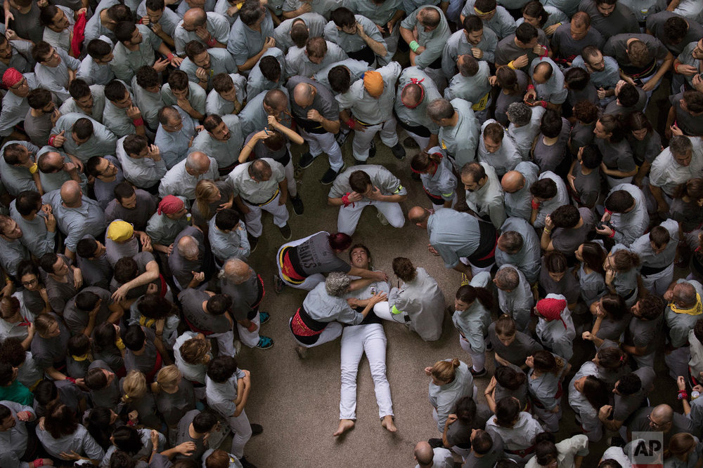 "A member of ""Castellers de Sants"" waits for medical assistance after being injured during their human tower during the 27th Human Tower Competition in Tarragona, Spain, Oct. 7, 2018. (AP Photo/Emilio Morenatti)"