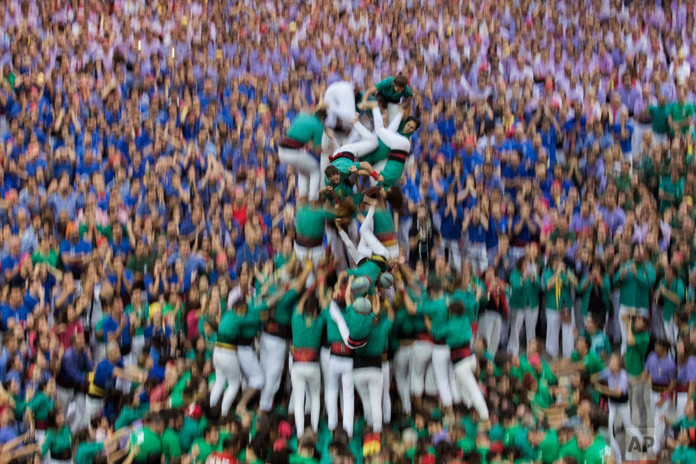 "Members of the ""Castellers de Sabadell"" fall as they try to complete their human tower during the 27th Human Tower Competition in Tarragona, Spain, Oct. 7, 2018. (AP Photo/Emilio Morenatti)"