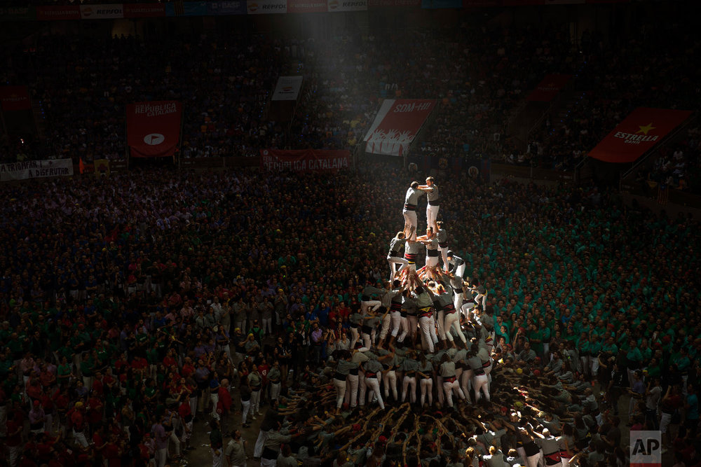 "Members of ""Castellers de Sants"" complete their human tower during the 27th Human Tower Competition in Tarragona, Spain, Oct. 7, 2018. (AP Photo/Emilio Morenatti)"