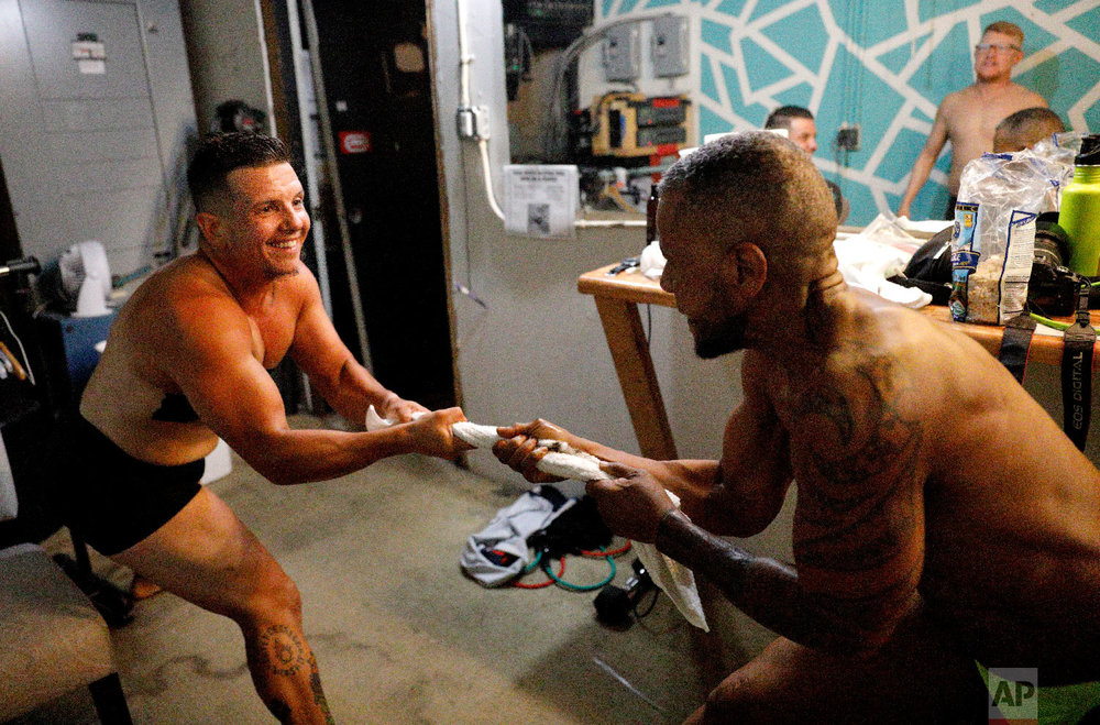 Charles Bennett, right, of San Francisco, plays tug-of-war with fellow contestant Devyn Michael Clark, of Jacksonville, Fla., to pump up their muscles backstage before the start of the International Association of Trans Bodybuilders competition in Atlanta, Oct. 6, 2018. (AP Photo/David Goldman)