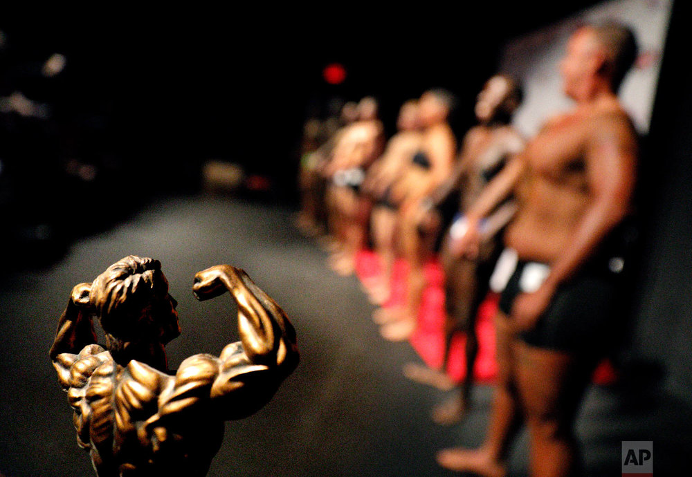 A trophy sits on display as contestants line up in front of the crowd at the International Association of Trans Bodybuilders competition in Atlanta, Oct. 6, 2018. (AP Photo/David Goldman)