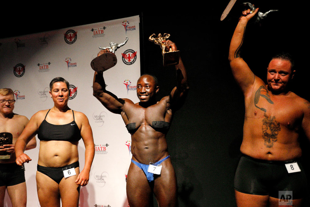 Wes Phills, of Brooklyn, N.Y., center, walks offstage after winning the overall award and middleweight class in the International Association of Trans Bodybuilders competition in Atlanta, Saturday, Oct. 6, 2018. At left are fellow competitors Peter Moore, and Sandy Baird, both of Oakland, Calif., and Kennedy Conners, right, of Conyers, Ga., who took home the heavyweight trophy. (AP Photo/David Goldman)