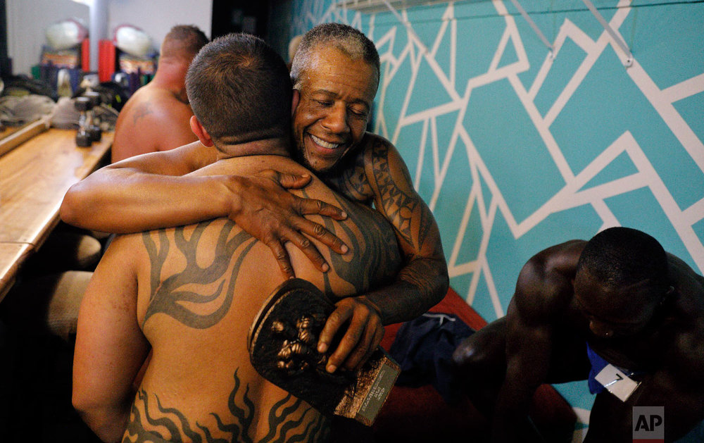 Charles Bennett, of San Francisco, center right, hugs Jai De Lotto, of Richmond, Calif., after they perform at the International Association of Trans Bodybuilders competition in Atlanta, Oct. 6, 2018. (AP Photo/David Goldman)