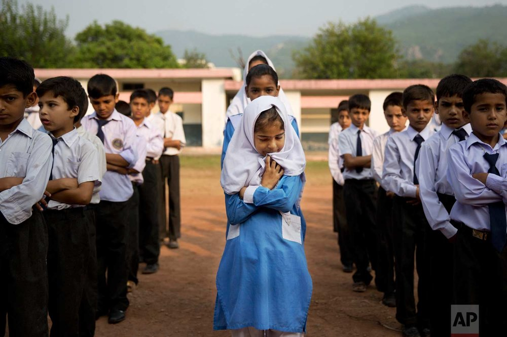 In this Oct. 11, 2013, photo, a Pakistani girl lines up among boys for their morning assembly where they sing the national anthem at a school in Islamabad, Pakistan. (AP Photo/Anja Niedringhaus)