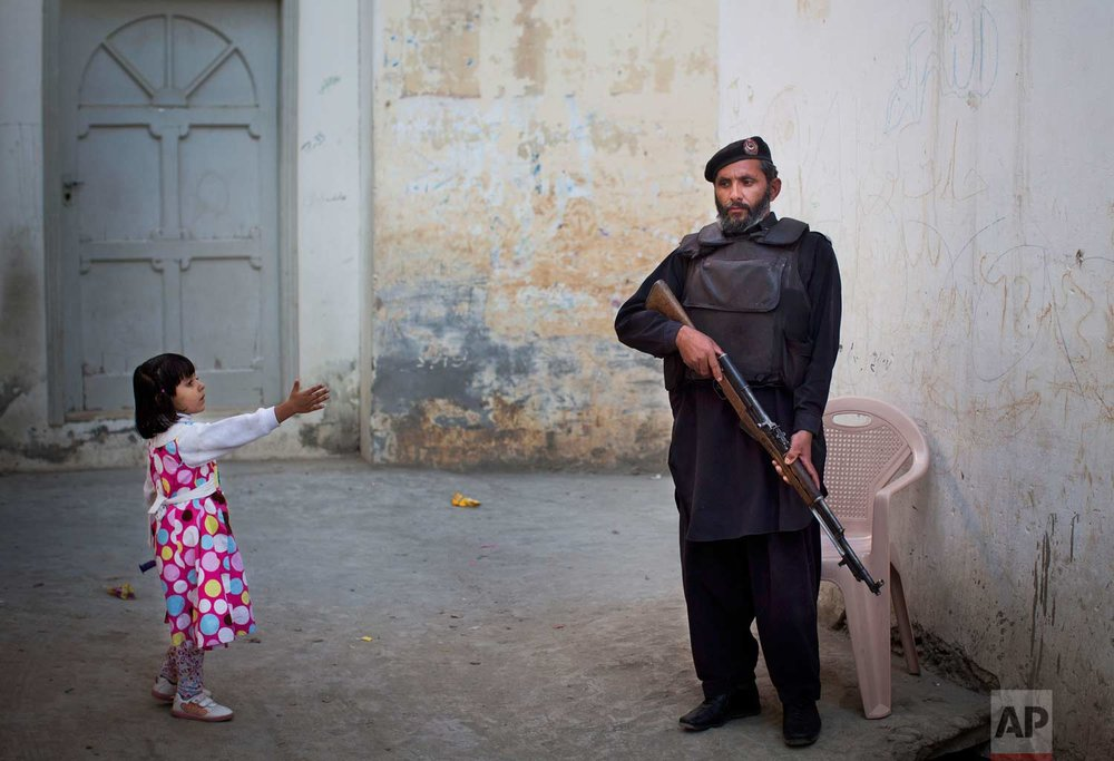 In this Wednesday, Nov. 15, 2012 photo, a young girl in her colorful dress reaches out to greet a Pakistani policeman securing the road outside Kainat Riaz's home in Mingora, Swat Valley, Pakistan. (AP Photo/Anja Niedringhaus)