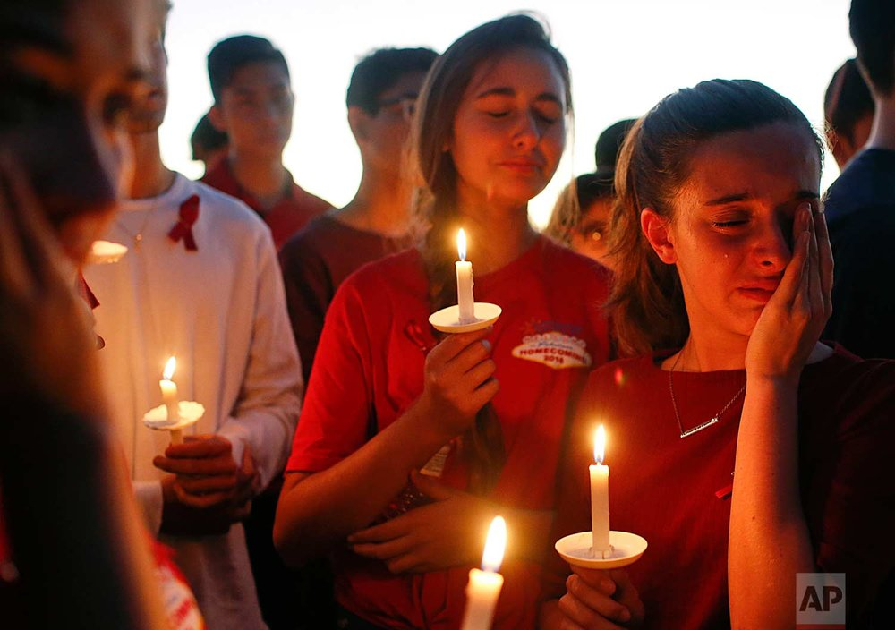 In this Feb. 15, 2018, photo, students gather to grieve during a vigil at Pine Trails Park for the victims of a shooting at Marjory Stoneman Douglas High School, in Parkland, Fla. (AP Photo/Brynn Anderson)