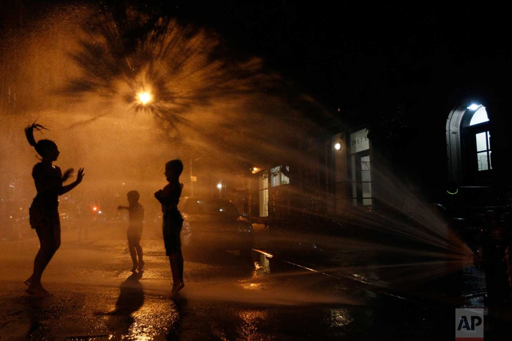 In this July 21, 2011, photo, Vanity Mendez, 11, left, Isaiah Rivera, 6, center, and Jonathan Medina, 11, cool off at an open fire hydrant in the East Village neighborhood of Manhattan. (AP Photo/Mary Altaffer)