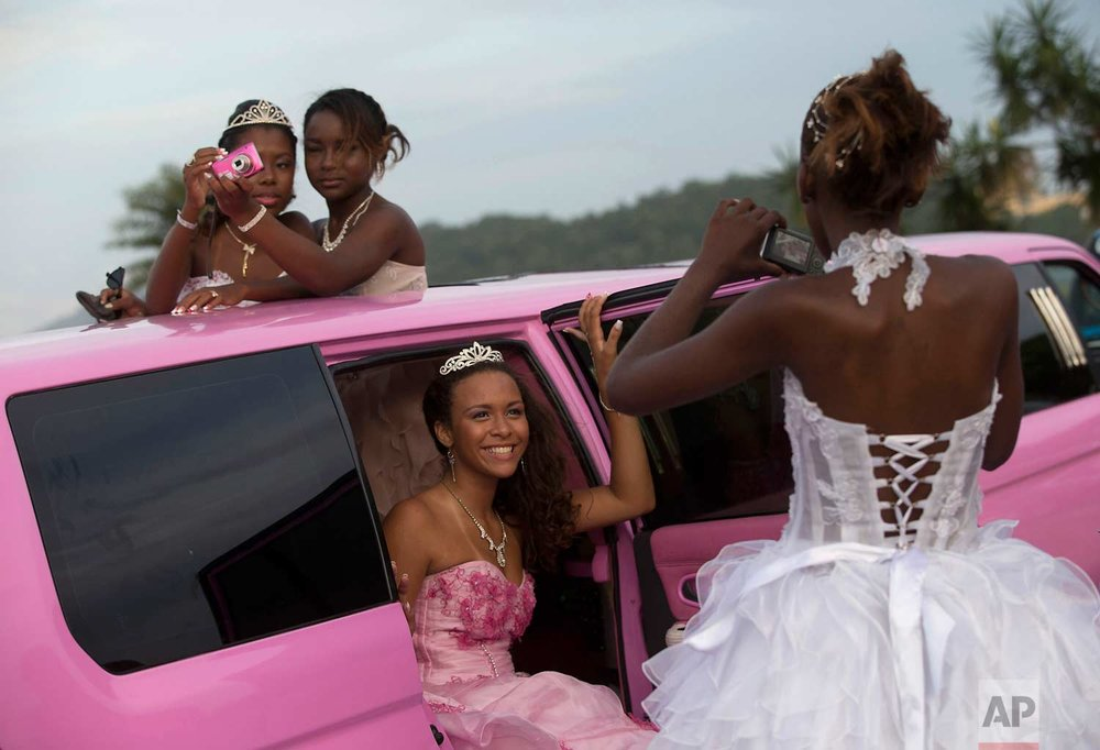 In this Nov. 8, 2012, photo, girls turning 15 pose in their gowns for photos inside a pink limousine before their debutante ball, organized by the Peacemaker Police Unit program in the Mangueira favela, or shantytown, in Rio de Janeiro, Brazil. The debutante ball marks girls' transition from childhood to adulthood and is common in Brazil and other Latin American countries. (AP Photo/Silvia Izquierdo)