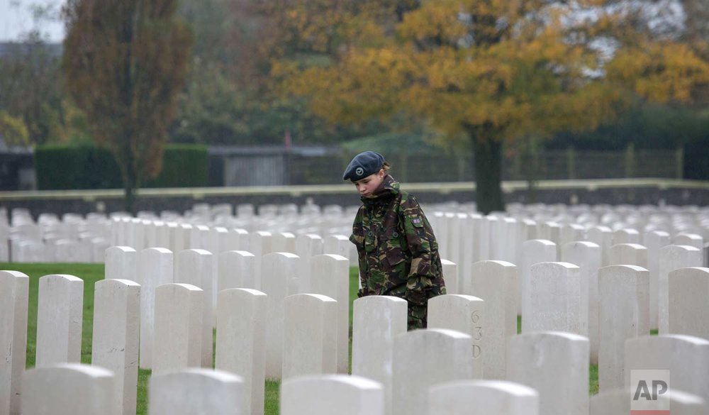 In this Nov. 12, 2013, photo, a young girl who is a member of the RAF cadets walks between gravestones at Tyne Cot World War One cemetery in Zonnebeke, Belgium. (AP Photo/Virginia Mayo)