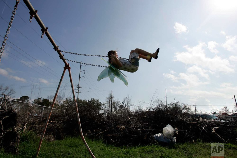 In this Feb. 25, 2006, photo, Nysa Loudon, 11, swings in the neighborhood park ravaged by Hurricane Katrina near her home in Gentilly area of New Orleans, La., 2006. She wears her angel wings for the Krewe of Druex Mardi Gras parade that will march through Gentilly. (AP Photo/Carolyn Kaster)