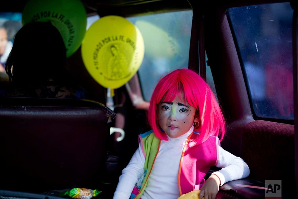 In this Dec. 14, 2015, photo, a young clown rides in the back of a car following a procession to the Basilica of Our Lady of Guadalupe in Mexico City. Hundreds belonging to various clown associations made their annual pilgrimage to the Basilica to pay their respects to the Virgin of Guadalupe, Mexico's patron saint. (AP Photo/Rebecca Blackwell)