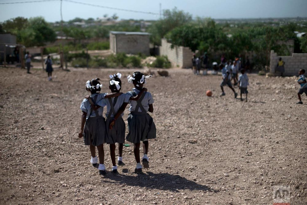 In this June 24, 2015, photo, schoolgirls walk through the rocky yard of Bethesda Evangelical School during a break in class, in Canaan, Haiti. (AP Photo/Rebecca Blackwell)