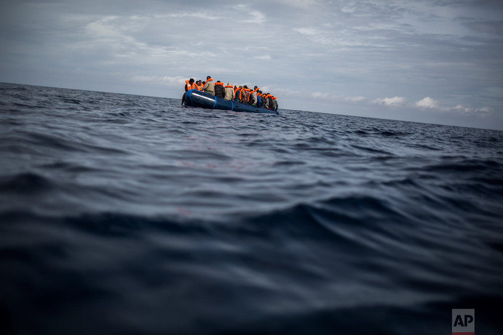 Migrants sit in a rubber dinghy after Proactiva Open Arms, a Spanish NGO, spotted and rescued them in the Alboran Sea, about 40 miles (64 kilometers) from the Spanish coast, on Thursday, Oct. 11, 2018. The group is now based at Motril port in order to start operating in the western Mediterranean area. (AP Photo/Javier Fergo)