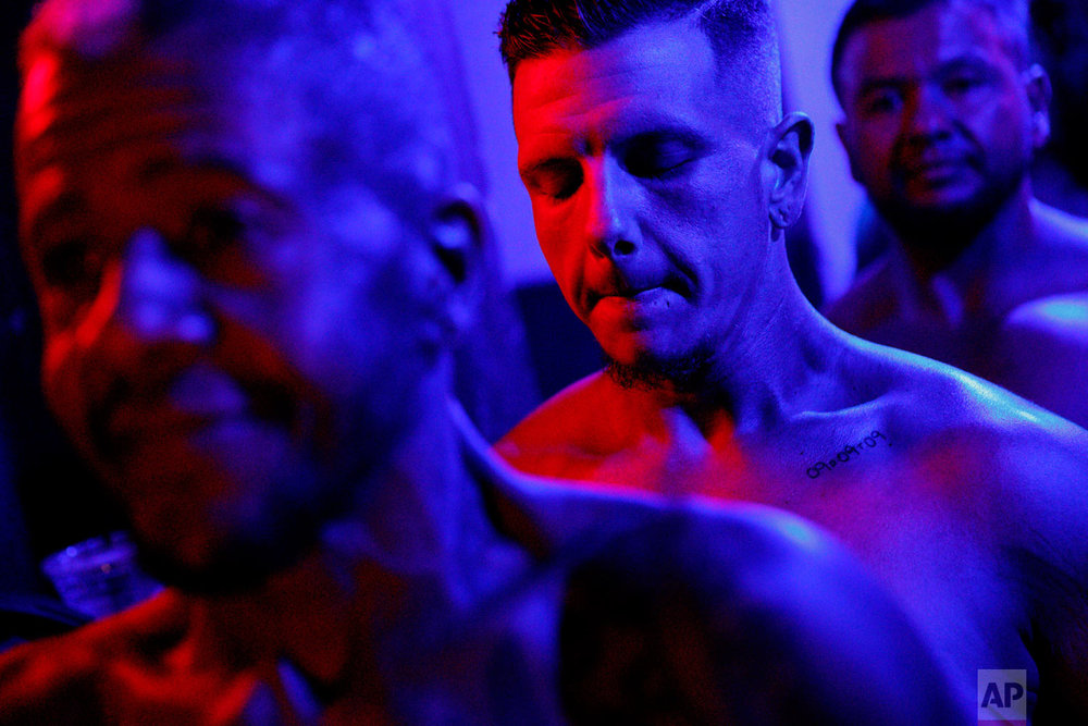 Devyn Michael Clark, of Jacksonville, Fla., center, closes his eyes for a moment backstage before the start of the International Association of Trans Bodybuilders competition in Atlanta, Saturday, Oct. 6, 2018. It's Clark's second year competing and he's lost 130 pounds from his training. (AP Photo/David Goldman)