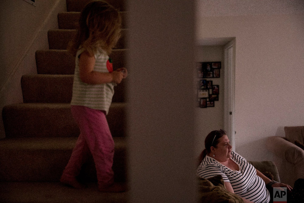 Middle-school English teacher Maryam Powers sits in her sofa as her 2-year-old daughter walks up the steps leading to the master bedroom in Salinas, Calif., on Sept. 5, 2018. (AP Photo/Jae C. Hong)