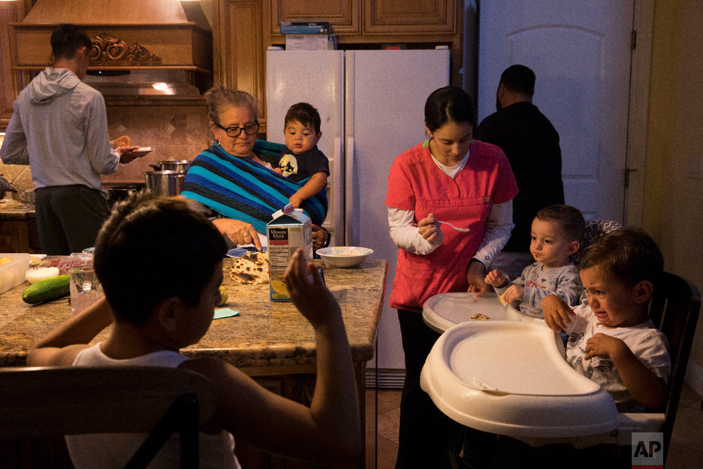 Lilia Coyt, center left, and Coyt's daughter-in-law, Araceli Nunez, feed babies in their four-bedroom home, where three generations and 15 members of the family are jammed into, in Salinas, Calif. (AP Photo/Jae C. Hong)