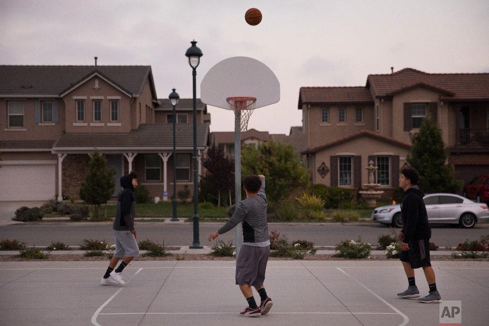 Three men play basketball at a park in front of newly built homes in Salinas, Calif., Sept. 3, 2018.(AP Photo/Jae C. Hong)