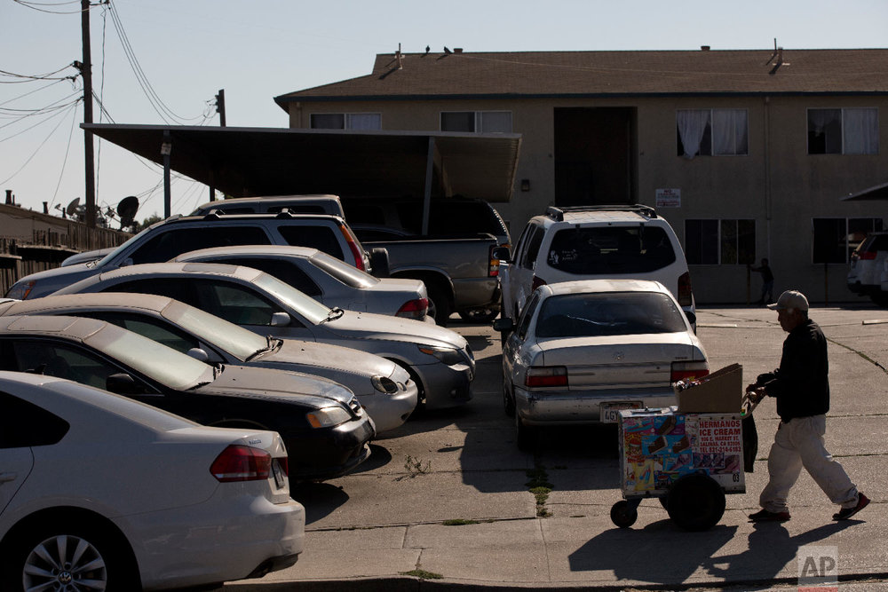 Cars are double-parked in the parking lot of an apartment complex in Salinas, Calif., Sept. 6, 2018. (AP Photo/Jae C. Hong)