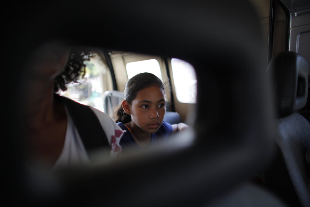 Angelis sits in a car with her mother Sandra Cadiz as they get a free ride on their journey to Peru on Sept. 2, 2018. (AP Photo/Ariana Cubillos)