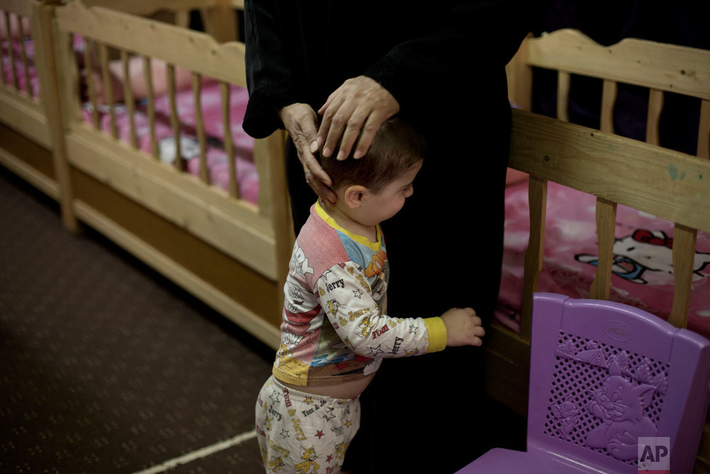 A worker comforts a toddler at the state-run Salhiya Orphanage in Baghdad, Iraq. (AP Photo/Maya Alleruzzo)