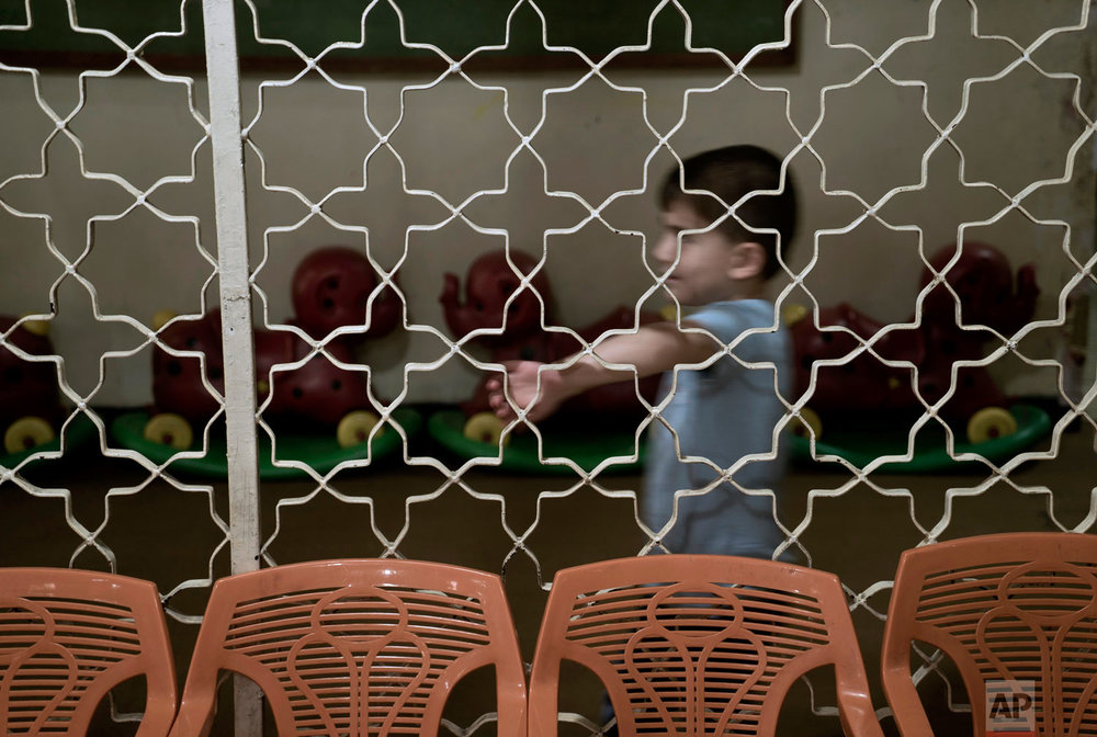 "A boy plays in the hallway at the state-run Salhiya Orphanage in Baghdad, Iraq. ""We have slowly changed their ideas and the way they think,"" said Abeer al-Chalabi, a senior government official in charge of social affairs in Baghdad. (AP Photo/Maya Alleruzzo)"
