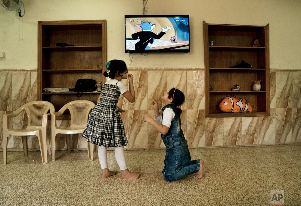 Two girls act out an episode from a Tom & Jerry cartoon at the state-run al-Zuhour Orphanage in Mosul, Iraq. (AP Photo/Maya Alleruzzo)