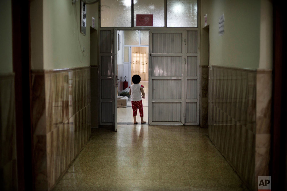 A girl wanders through a hallway at the state-run al-Zuhour orphanage in Mosul, Iraq. (AP Photo/Maya Alleruzzo)