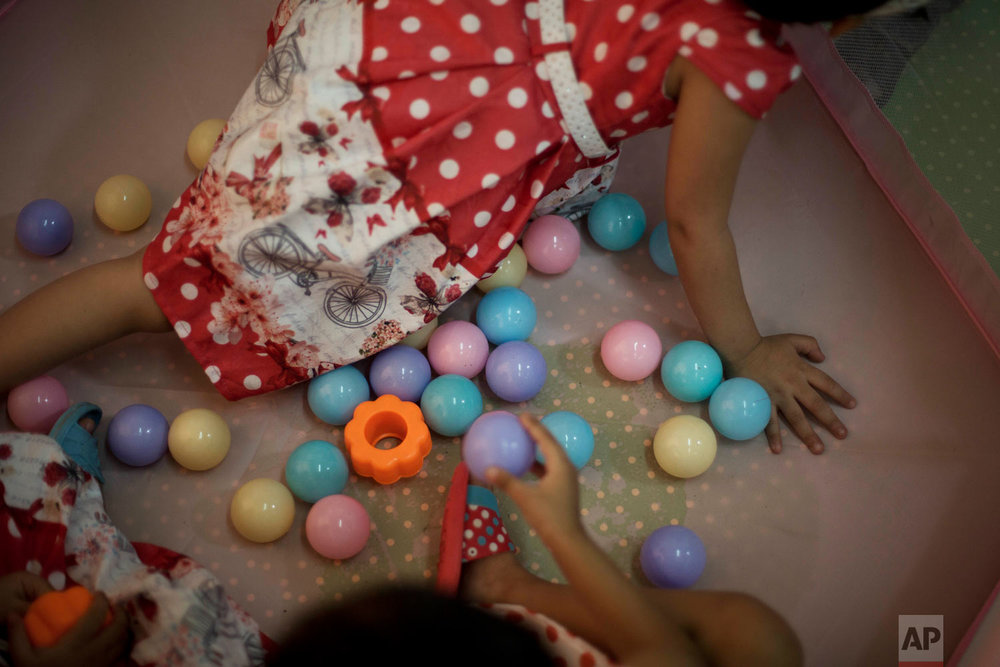 Girls play in a playpen at Salhiya Orphanage in Baghdad, Iraq. (AP Photo/Maya Alleruzzo)