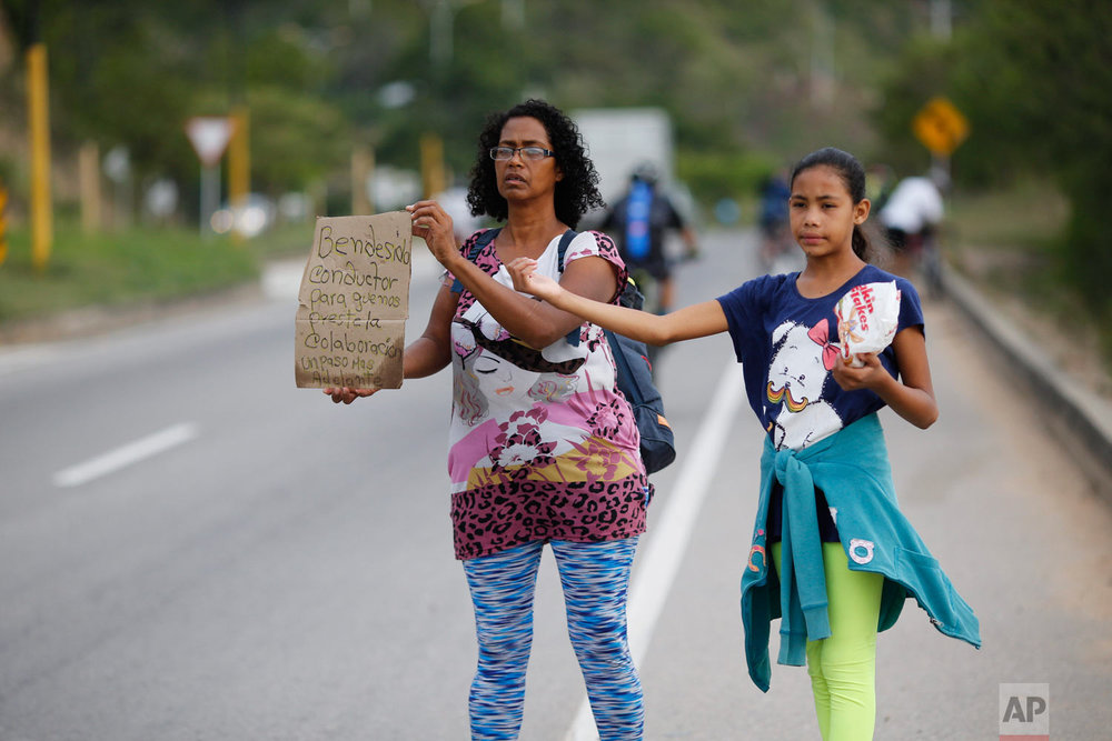 """In this Sept. 2, 2018 photo, Venezuelan Sandra Cadiz holds up her handmade sign carrying the Spanish message: """"Blessed driver, please help us with a ride,"""" as her 10-year-old daughter Angelis stands with her on the road leaving Giron, Colombia, as they make their way to Peru. As rising numbers of Venezuelans flee, those who cannot afford a plane or bus ticket out are going by foot. (AP Photo/Ariana Cubillos)"""