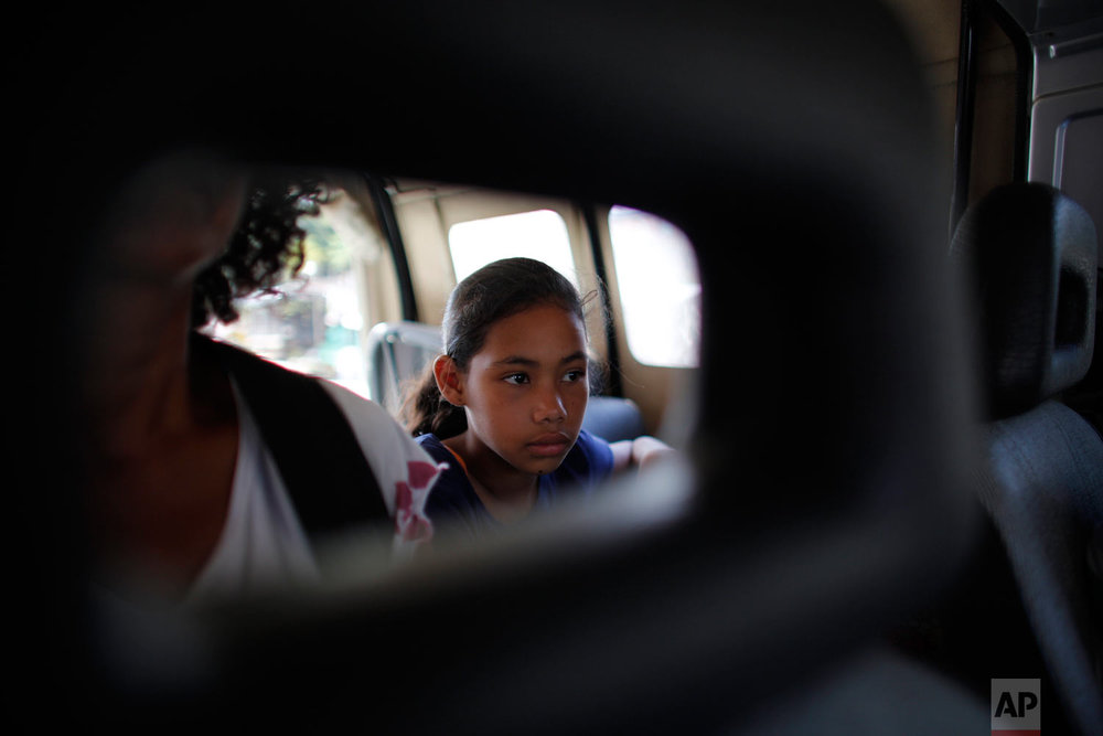 In this Sept. 2, 2018 photo, 10-year-old Venezuelan Angelis sits in a car with her mother Sandra Cadiz as they get a free ride from a driver to the next city, Lebrija, Colombia, on their journey to Peru. A police officer offered to hail down a ride, and a man in an old boxy Chevrolet Samurai agreed to take them. (AP Photo/Ariana Cubillos)