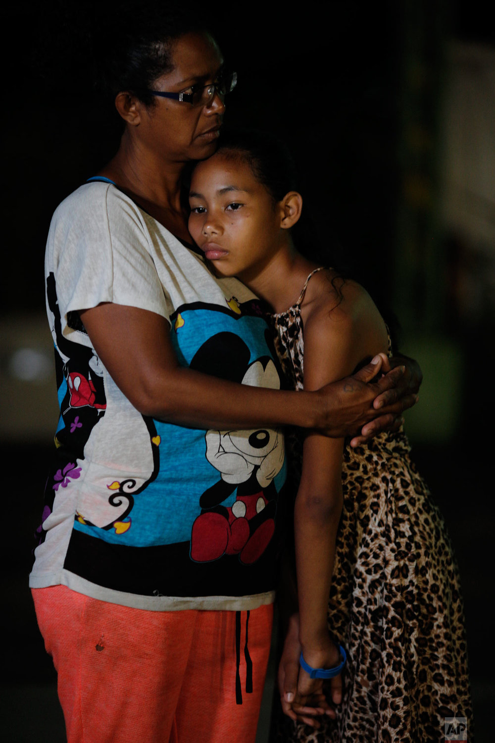 """In this Sept. 4, 2018 photo, Venezuelan Sandra Cadiz and her 10-year-old daughter Angelis embrace after spending the night outside a Biomax gas station in a remote stretch of farmland known only as """"Kilometer 17"""" in Santander state, Colombia, on their journey to Peru. A doctor had recently told Cadiz that her daughter was malnourished. The skinny 10-year-old was at least 10 pounds underweight and only eating twice a day. (AP Photo/Ariana Cubillos)"""