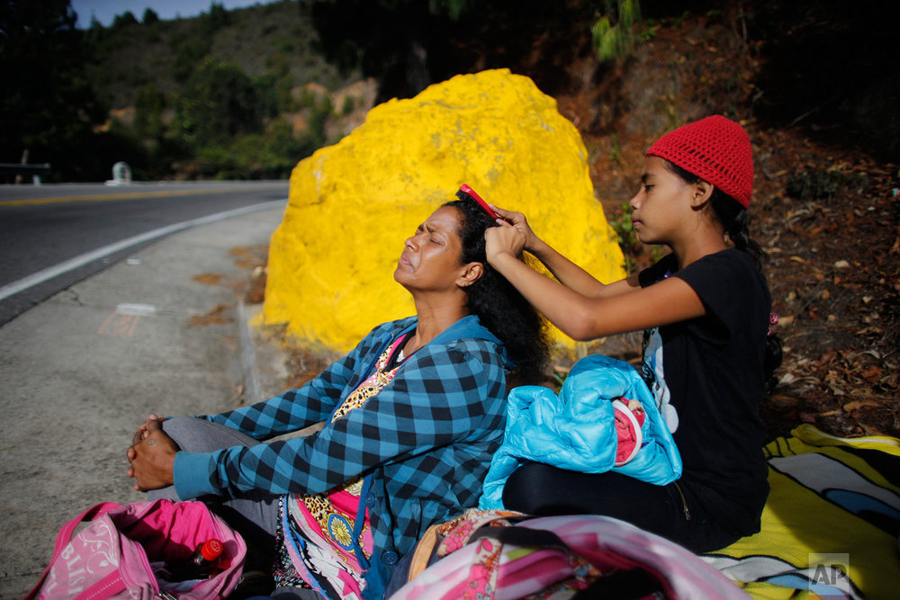 In this Sept. 1, 2018 photo, 10-year-old Venezuelan Angelis combs the hair of her mother Sandra Cadiz as they take a break from walking to the Berlin paramo, which leads to the city of Bucaramanga, Colombia, on their journey to Peru. The daughter of a housewife and a cemetery worker, Cadiz had grown up to know great misfortune, but she had never expected to know exile. (AP Photo/Ariana Cubillos)