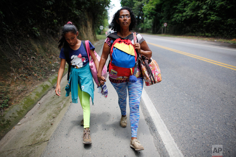 In this Sept. 2, 2018 photo, Venezuelan Sandra Cadiz holds the hand of her 10-year-old daughter Angelis as they walk on the shoulder of the road during their journey to Peru, near Dagota, Colombia. When Sandra Cadiz began struggling to feed her daughter, she knew it was time to leave Venezuela. (AP Photo/Ariana Cubillos)