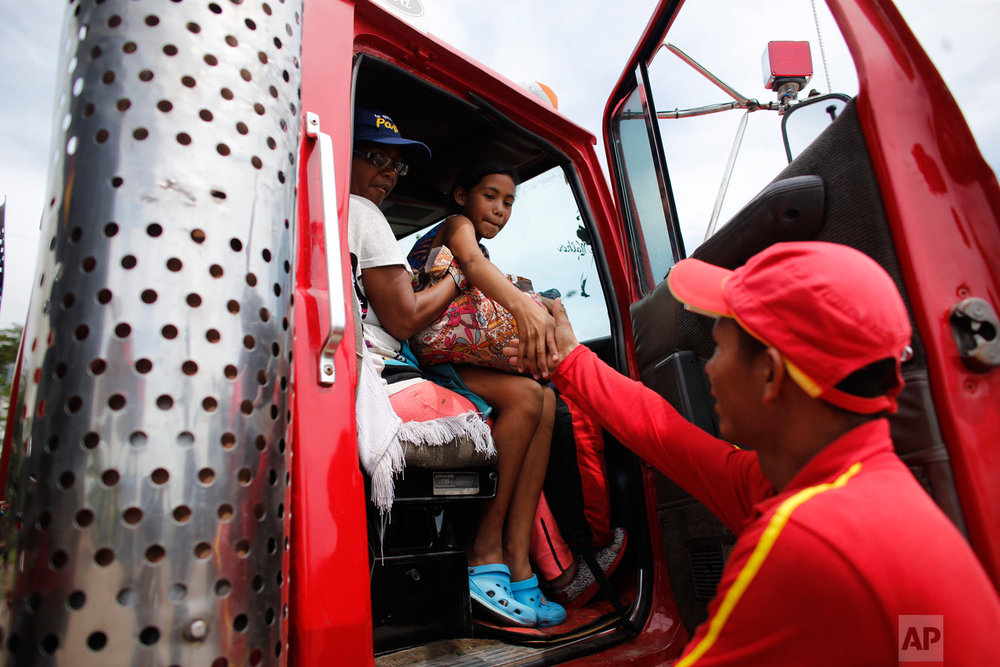 In this Sept. 3, 2018 photo, Venezuelan Sandra Cadiz and her 10-year-old daughter Angelis, thank gas station worker Manuel Velasquez after he helped them get a ride in the cabin of a truck in Peroles, Colombia, on their journey to Peru. Whenever the two got a ride in the cabin of a truck, Cadiz made a point of seating her daughter closest to the passenger door, putting herself as a protective layer between the driver and her daughter. (AP Photo/Ariana Cubillos)