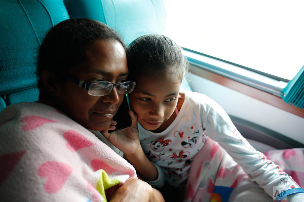In this Sept. 5, 2018 photo, Venezuelan Sandra Cadiz listens to a voice message from her son Leonardo as she and her 10-year-old daughter Angelis take a bus from Cali to Ipiales, Colombia. After five days of walking and hitching rides they had gathered enough money from generous Colombians to begin buying bus tickets. The ride took them one border closer toward reaching Peru, where they hoped to reunite with Leonardo and his family. (AP Photo/Ariana Cubillos)