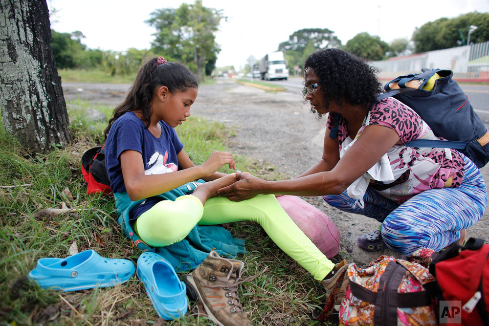 """In this Sept. 2, 2018 photo, Venezuelan Sandra Cadiz inspects the foot of her 10-year-old daughter Angelis who complained of pain as they take a break from their walk to Peru along the shoulder of the road near Dagota, Colombia. When President Nicolas Maduro announced he'd give those with a """"Fatherland Card"""" a special bonus, Cadiz saw an opportunity to buy two bus tickets to the Colombia border or purchase her daughter a pair of new shoes. """"Let's go, mama,"""" Angelis told her. """"I'll walk in my broken shoes."""" (AP Photo/Ariana Cubillos)"""