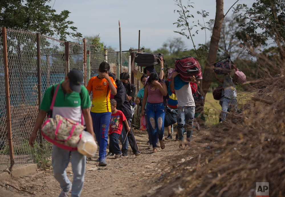 """In this Aug. 31, 2018 photo, Venezuelans illegally cross into Colombia, to Villa del Rosario, along a path known as a """"trocha."""" Uncontrolled by Venezuelan or Colombian authorities, the trochas are ruled by bands of armed men sporting rifles and dressed in fatigues. They charge migrants about $10 to be let through, frequently robbing or assaulting those who can't pay. (AP Photo/Ariana Cubillos)"""