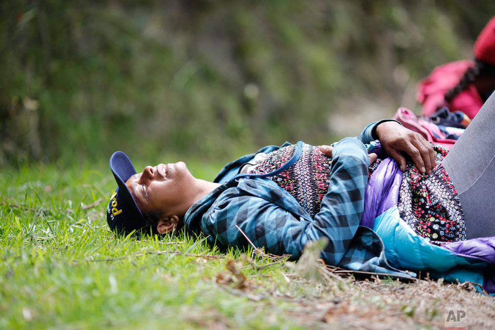 In this Sept 1, 2018 photo, fatigued Venezuelan Sandra Cadiz throws herself on the grass as she takes a break from walking to the Berlin paramo leading to the city of Bucaramanga, Colombia, on her journey to Peru. Like a growing number of desperate Venezuelans, Cadiz and her 10-year-old daughter journeyed by foot, risking their lives as they set out to cross an unforgiving terrain of frigid mountaintops, scorching rural valleys and perilous border crossings. (AP Photo/Ariana Cubillos)