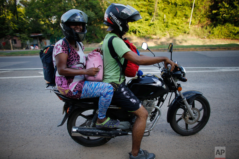 In this Sept. 2, 2018 photo, Venezuelan Sandra Cadiz gets a free ride from a motorcyclist to Peroles, Colombia, on her journey to Peru. The driver then returned for her 10-year-old daughter. Nine days and nearly two thousand miles after fleeing Caracas, Cadiz and her 10-year-old daughter reached the final border they'd set out to cross. (AP Photo/Ariana Cubillos)