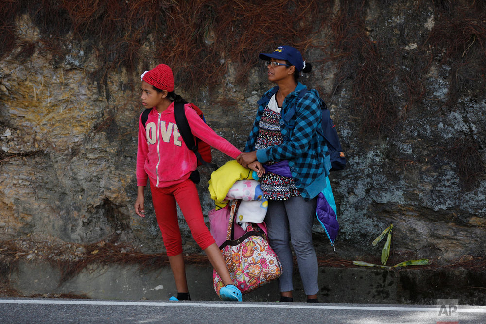 In this Sept. 1, 2018 photo, Venezuelan Sandra Cadiz holds the hand of her 10-year-old daughter, who's scared of the trucks racing by, as they wait for an opportunity to cross a highway on their way to the Berlin paramo, which leads to the city of Bucaramanga, Colombia, on their journey to Peru. Of the millions of Venezuelans who have fled their nation's spiraling hyperinflation, deadly medical shortages and withering democracy in an exodus that rivals even the European refugee crisis in numbers, they were the least fortunate: The ones who could not afford the comfort of a bus or plane. (AP Photo/Ariana Cubillos)
