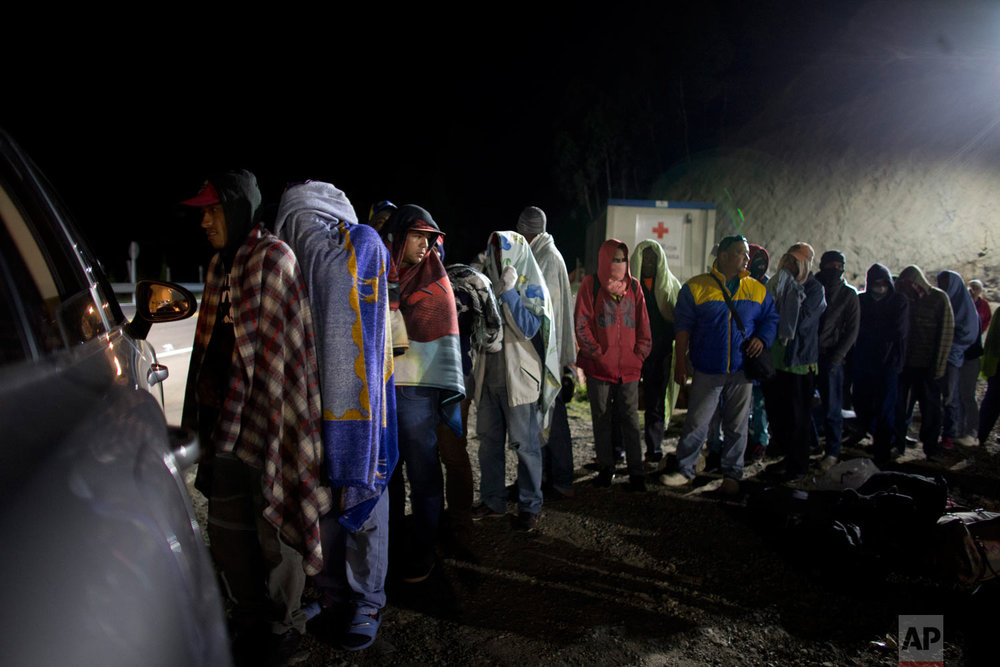 In this Aug. 31, 2018 photo, Venezuelan migrants line up for free bread and coffee, donated by a Colombian family from their car, at a gas station in Pamplona, Colombia. Millions have fled Venezuela's deadly shortages and spiraling hyperinflation in an exodus that rivals even the European refugee crisis in numbers. (AP Photo/Ariana Cubillos)