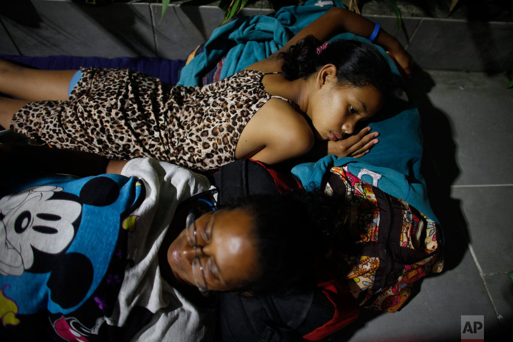 """In this Sept. 3, 2018 photo, Venezuelan Sandra Cadiz and her 10-year-old daughter Angelis, lie on the floor of a gas station where they spent the night at a place known only as """"Kilometer 17"""" in Santander state, Colombia, on their journey to Peru.All through the night it rained and thundered. Water blew onto their blankets, forcing them to repeatedly get up and move to whichever edge of the gas station had managed to stay dry. (AP Photo/Ariana Cubillos)"""