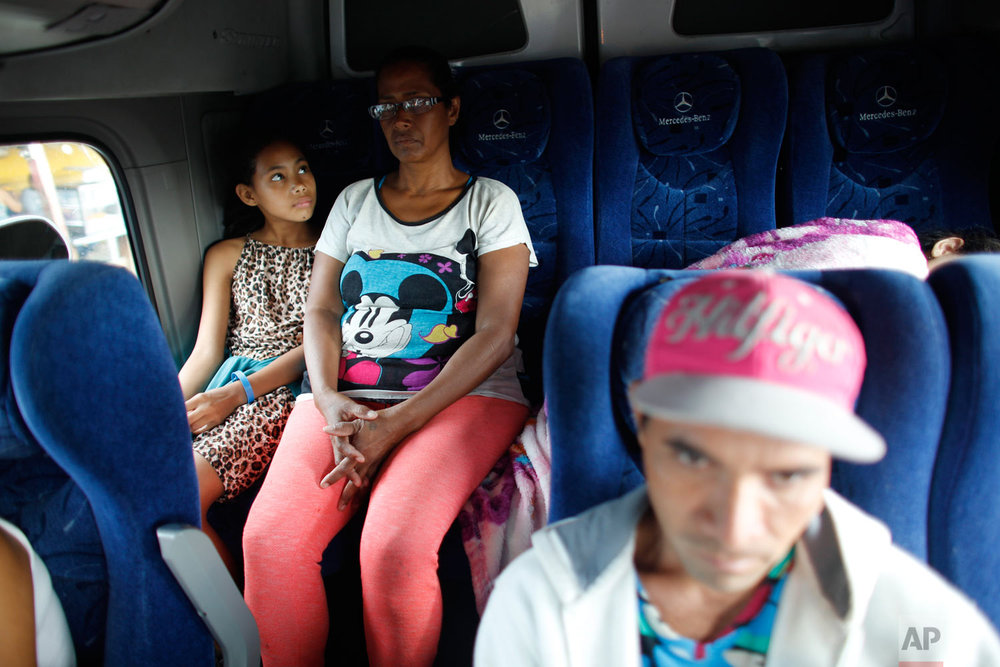 In this Sept. 4, 2018 photo, 10-year-old Venezuelan Angelis looks up at her mother Sandra Cadiz on the back of a bus at the stop in San Juan de la Paz, Colombia, on their journey to Peru. It was in San Juan De La Paz that Cadiz decided to switch her strategy: She'd barter with the 250,000 or so pesos - about $80 - she'd now collected from generous Colombians who'd spotted her walking and given her money to buy her way on to buses. (AP Photo/Ariana Cubillos)